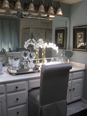 Modern High Back Vanity Chair Dressed In Gray Vinyl Skirted Slipcover Blends Harmoniously With White Cabinet The Entire Wall Is Occupied By Crystal