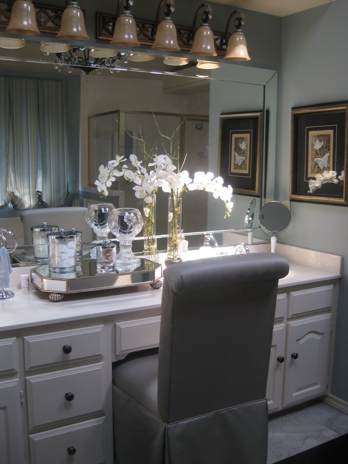Modern High Back Vanity Chair Dressed In Gray Vinyl Skirted Slipcover  Blends Harmoniously With White Vanity Cabinet. The Entire Wall Is Occupied  By Crystal ...