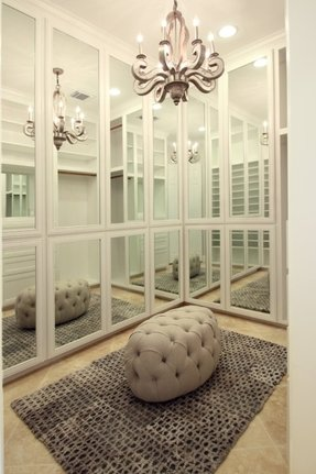 Chic closet with floor to ceiling mirrored closet doors and