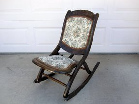 Antique mahogany folding rocking chair with floral patterned seat and