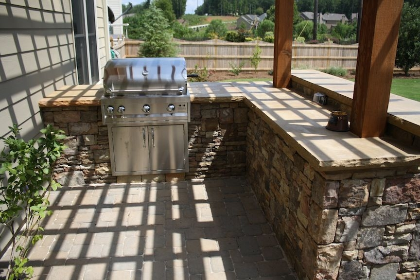 Stacked Stone L Shaped Outdoor Kitchen With Attached Pergola And