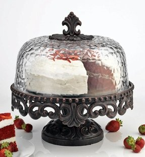 Scrolled metal cake stand with hammered glass dome footed cake