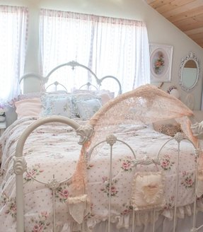 Iron bed frame including pink flowery bed sheets and white