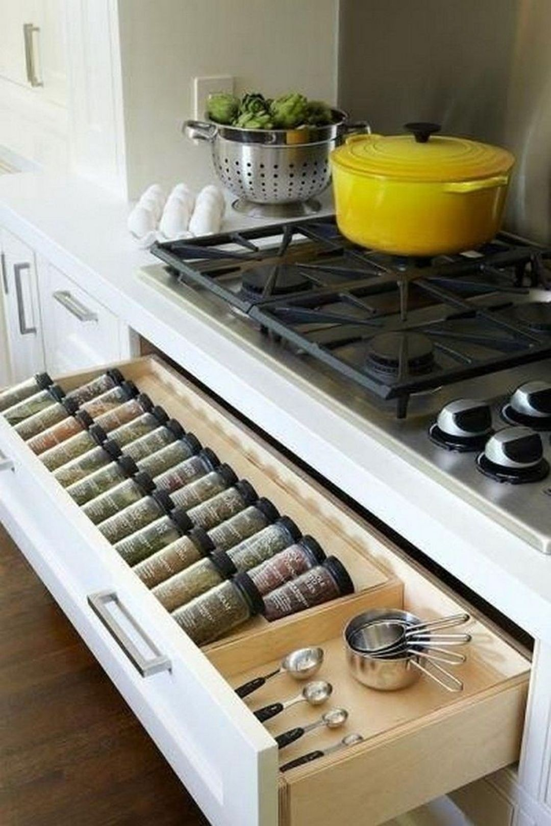 Kitchen with spice rack drawer below gas cooktop well organized