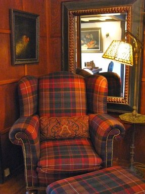 Plush red plaid armchair with rolled arms stud details and